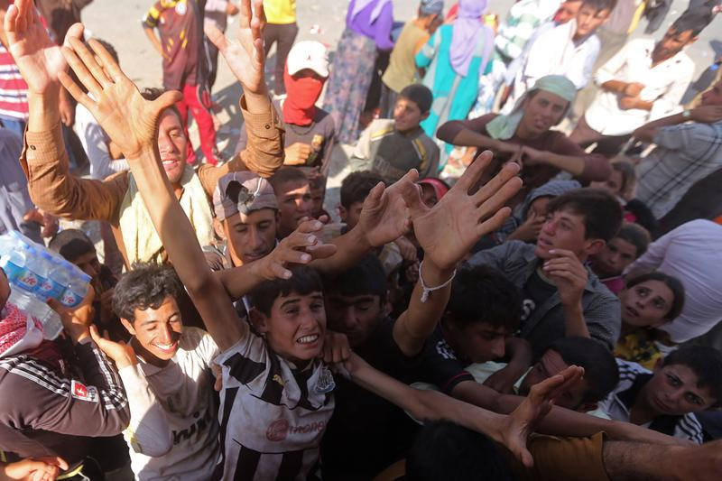 Displaced Iraqi Yazidis, who fled a jihadist onslaught on Mt. Sinjar, gather to collect bottles of water at the Bajid Kandala camp in Kurdistan's western Dohuk province, on August 13. Scores of young men and children held a protest demanding more aid at the Bajid Kandala camp that is hosting thousands of desperate Iraqi Yazidis. (Ahmad Al-Rubaye/AFP/Getty Images)
