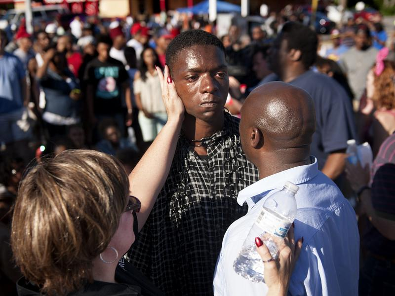 The Rev. Willis Johnson (right) confronts Joshua Wilson, 18, as protesters block traffic during a demonstration against the death of 18-year-old Michael Brown in Ferguson, Mo., on Wednesday. Rev. Johnson convinced Wilson, one of the last holdouts in the intersection, that he should leave and avoid arrest.
