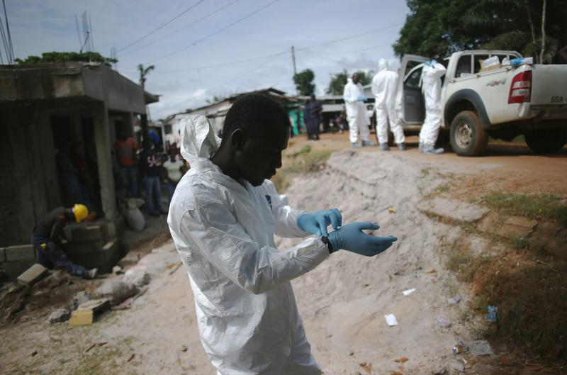 A burial team prepares to collect the dead body of a woman suspected of dying of the Ebola virus on August 14, 2014 in Monrovia, Liberia. Teams of undertakers wearing protective clothing are collecting victims from all over the capital Monrovia, where the spread of the highly contagious and deadly Ebola virus has been called catastrophic. The epidemic has killed more than 1,000 people in four West African countries. (John Moore/Getty Images)