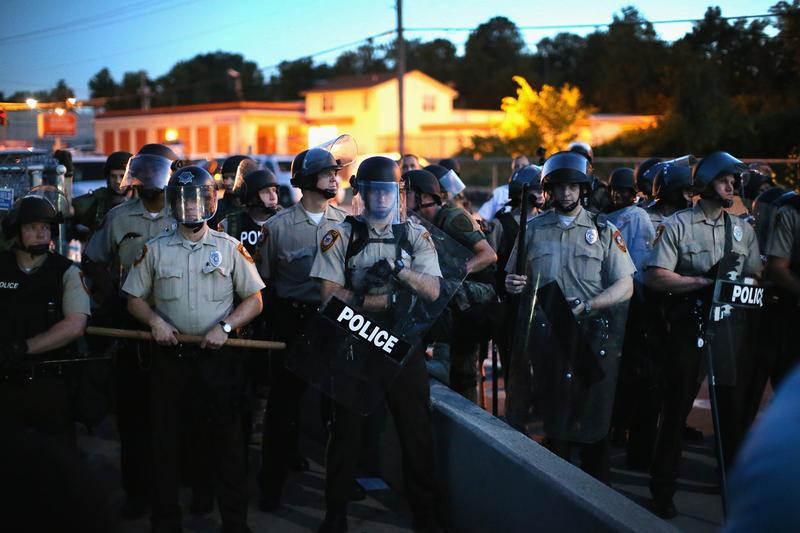 Police stand watch as demonstrators protest the shooting death of teenager Michael Brown on August 13 in Ferguson, Missouri. Brown was shot and killed by a Ferguson police officer on Saturday. (Scott Olson/Getty Images)