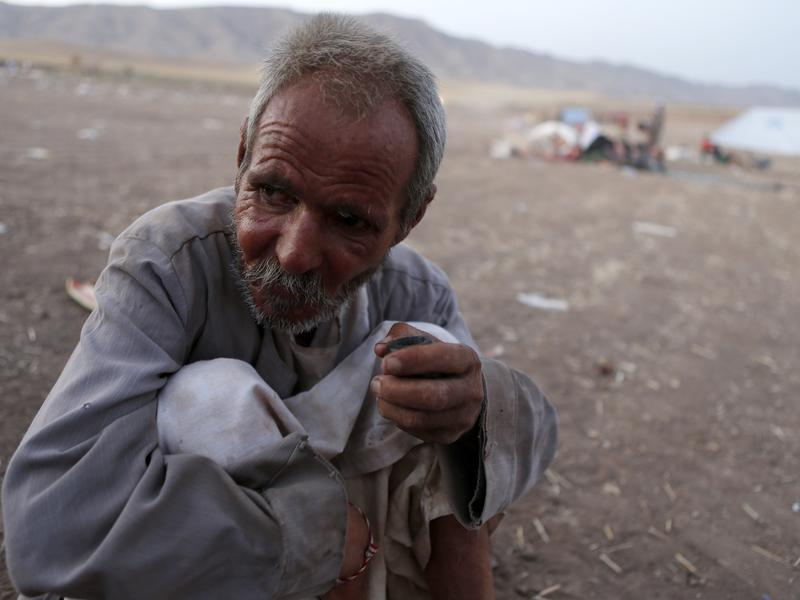A man from the minority Yazidi sect, who fled the violence in the Iraqi town of Sinjar, sits on the ground at Bajed Kadal refugee camp southwest of Dohuk province on Friday.