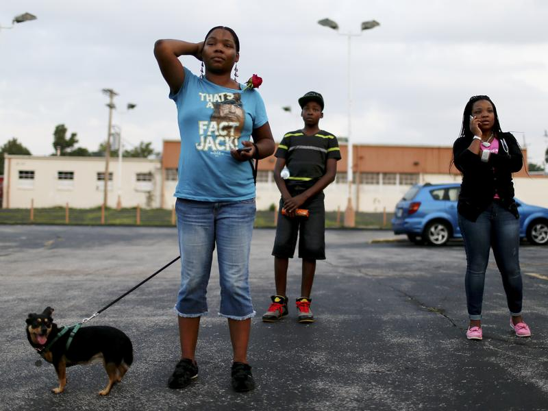 Demonstrators protesting the shooting death of Michael Brown listen to rapper Nelly speak.