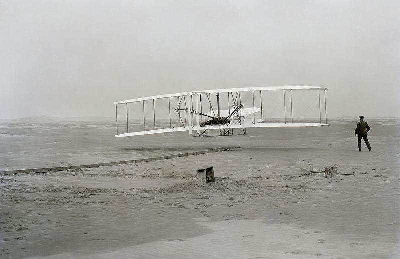First flight of the Wright Flyer I, December 17, 1903, Orville piloting, Wilbur running at wingtip. (John T. Daniels/Wikimedia Commons)