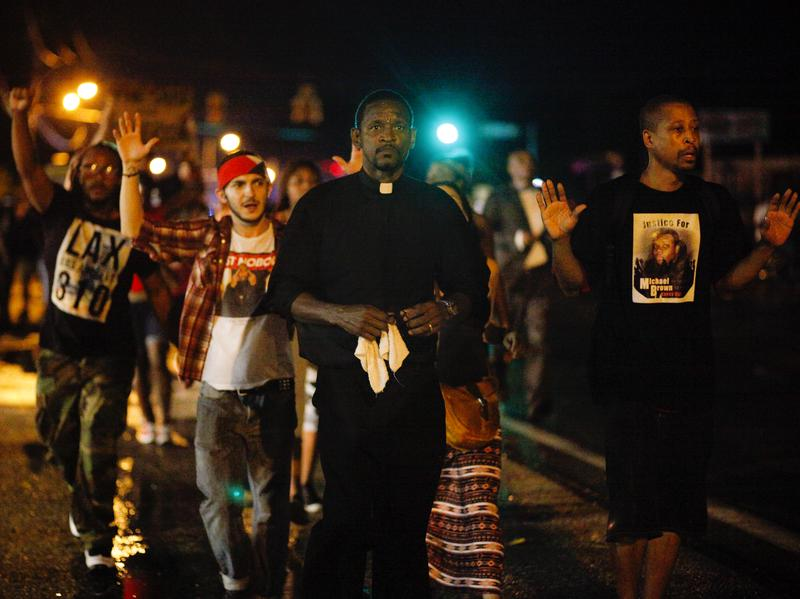 A clergyman leads demonstrators protesting the shooting death of Michael Brown down West Florissant Avenue in Ferguson, Mo., on Wednesday. A large contingent of clergy helped keep the mood calm after days of unrest.