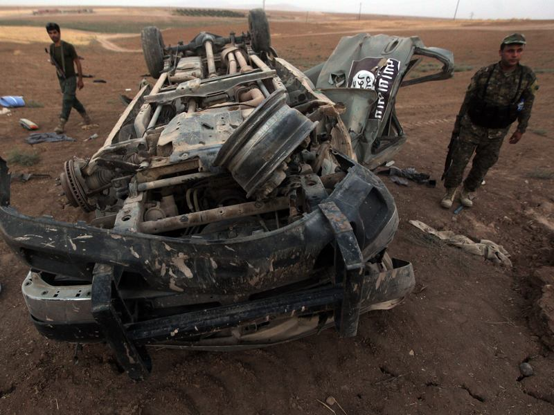 Peshmerga fighters inspect the remains of a car bearing an image of the trademark jihadist flag, after it was targeted by an American airstrike in the village of Baqouba, north of Mosul. The car reportedly belonged to Islamic State militants