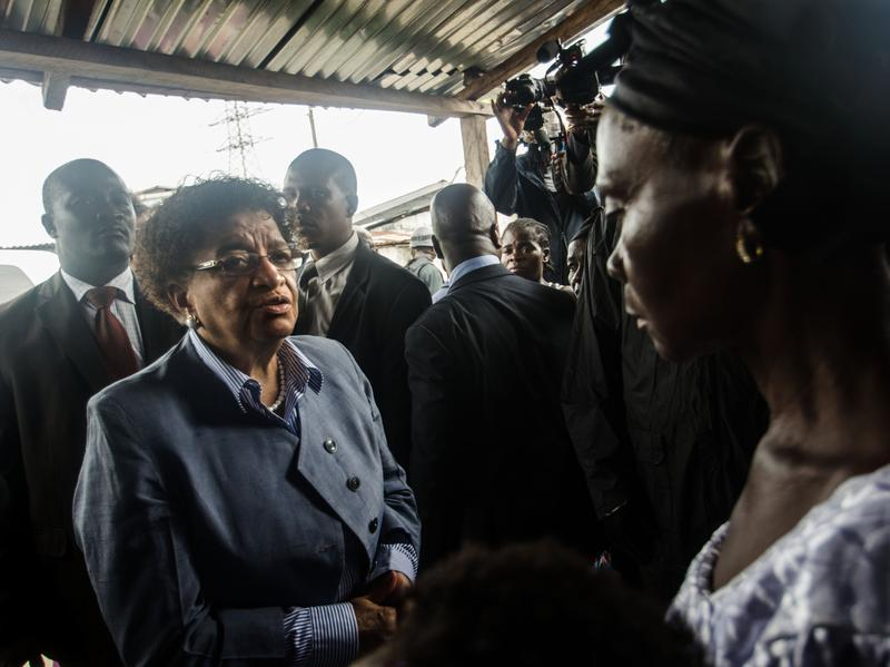 President Ellen Johnson Sirleaf apologizes to Eva Kamara, the mother of a boy who was shot by Liberian security forces last week and later died.