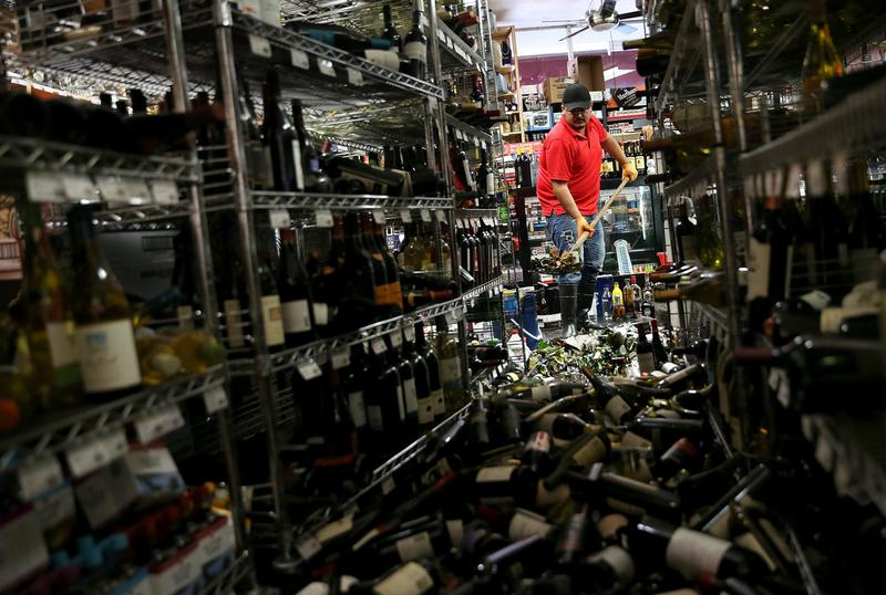 Eddie Villa uses a shovel to clean up wine bottles that were thrown from the shelves at Van's Liquors following a reported 6.0 earthquake on August 24, 2014 in Napa, California. (Justin Sullivan/Getty Images)
