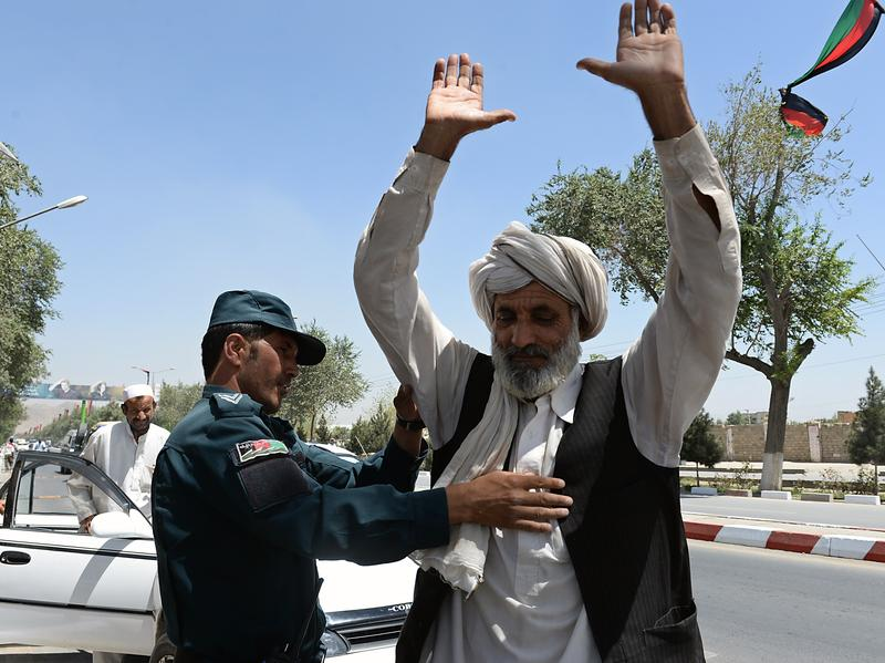 An Afghan policeman searches a man at a checkpoint where a NATO soldier was stabbed to death in Kabul on Aug. 20. As U.S. and NATO troops are drawing down in Afghanistan, the Taliban have been stepping up attacks this summer.