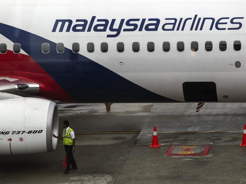 A Malaysia Airlines crew-member inspects an airplane at Kuala Lumpur International Airport (KLIA) on Thursday. The carrier announced it was laying off a third of its workforce amid steep financial losses.