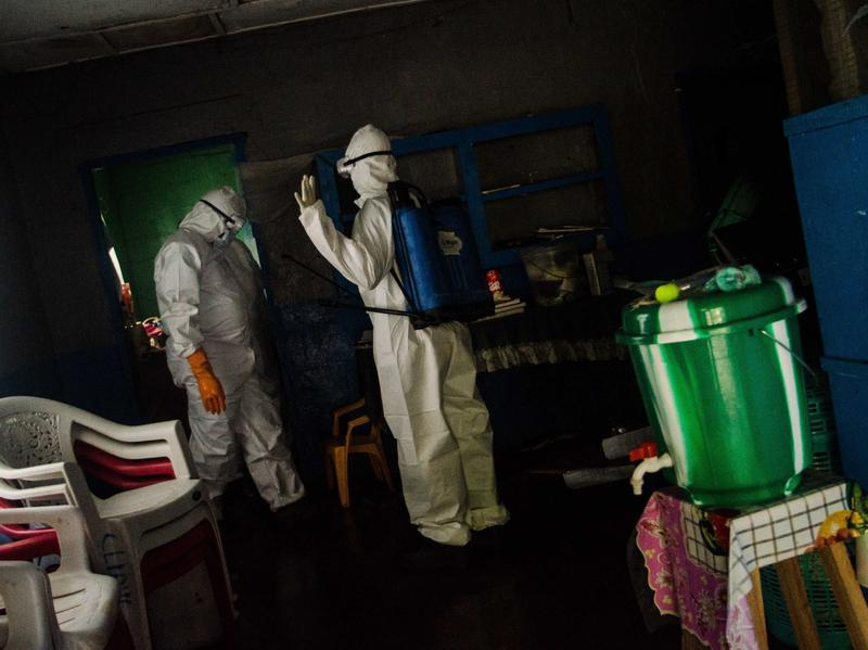 Body collectors come to the home of four children in Monrovia who lost both parents to Ebola.