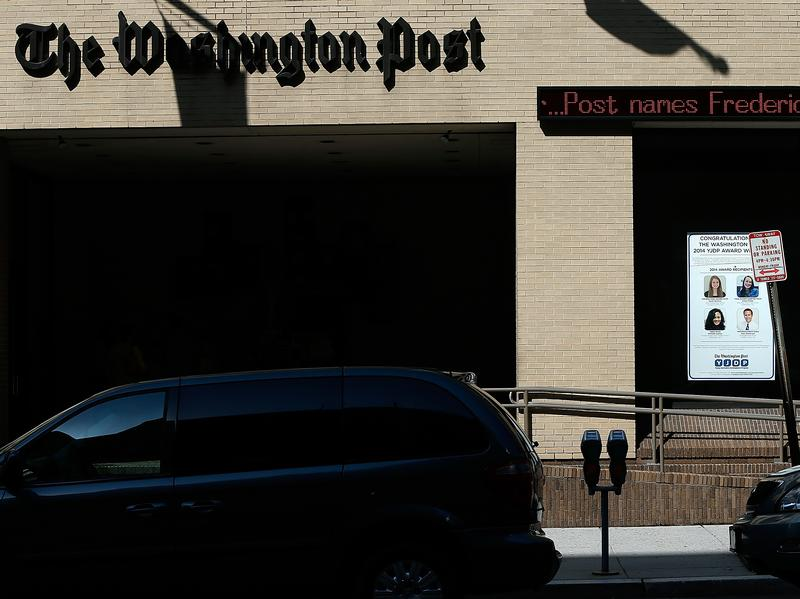A man walks past the Washington Post building on Tuesday in Washington, D.C.