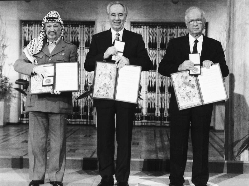 """Palestinian leader Yasser Arafat (from left), Israeli Foreign Minister Shimon Peres and Israeli Prime Minister Yitzhak Rabin pose with their medals and diplomas after receiving the 1994 Nobel Peace Prize on Dec. 10, 1994. The three were awarded the prize for """"for their efforts to create peace in the Middle East."""""""