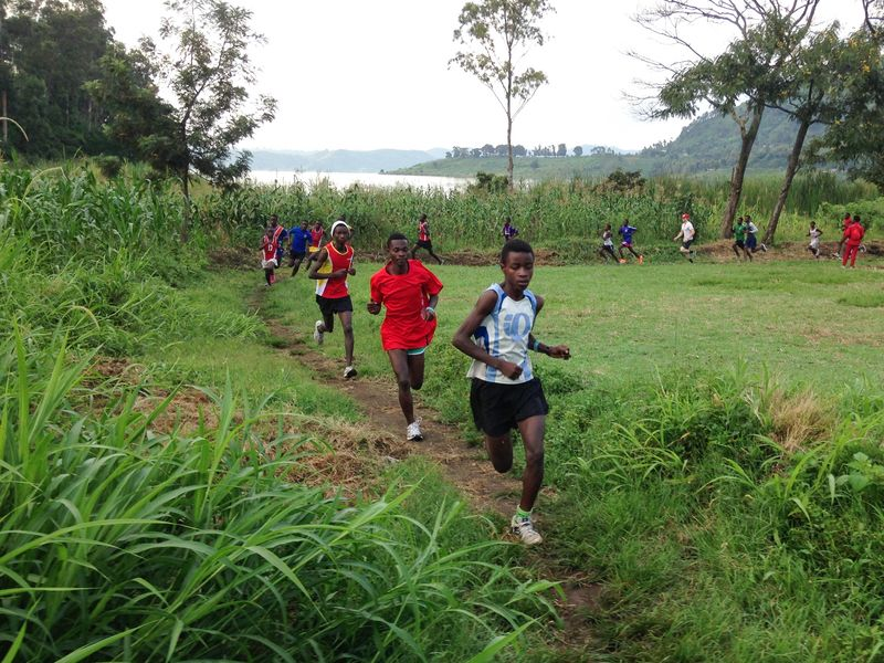 The runners in Project Kirotshe take off through forested mountains. For participating in the club, they each get a stipend to pay school fees.