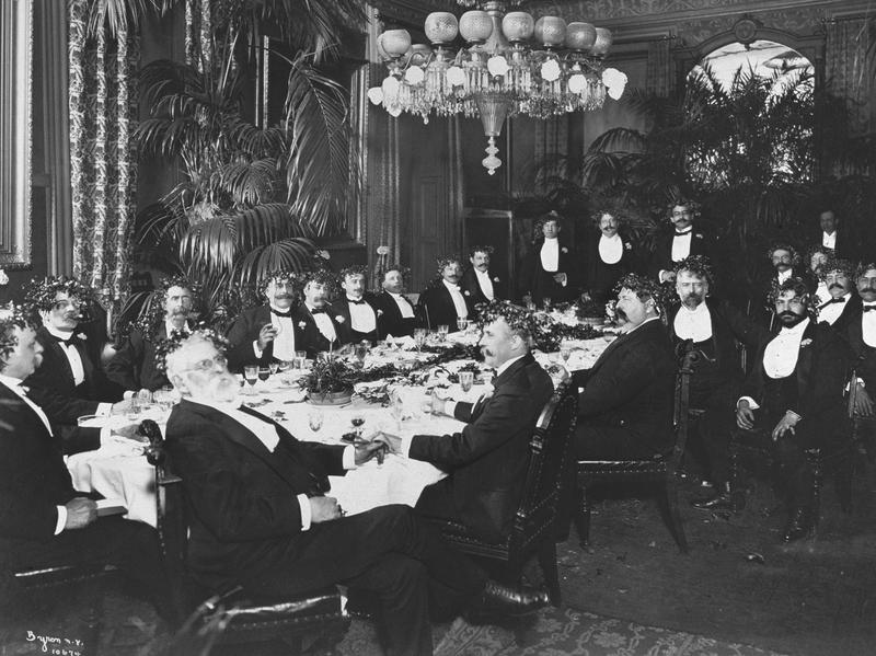 Circa 1900: Men in formal evening attire dine at the Montauk Club in New York.