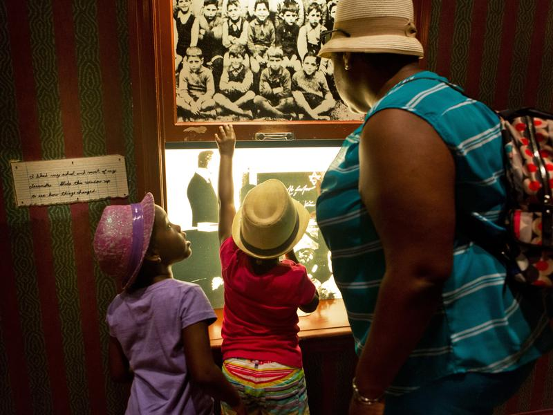 (Top left) A loaf of bread that Daniel's family ate for their meals while they lived in the ghetto. (Top right) Aiden reads one of Daniel's diary entries. Twin sisters Nicolette and Victoria Dejour, 6, look through a window displaying scenes of Germany with their mother, Royann, in the children's exhibit at the Holocaust Museum in Washington, D.C.