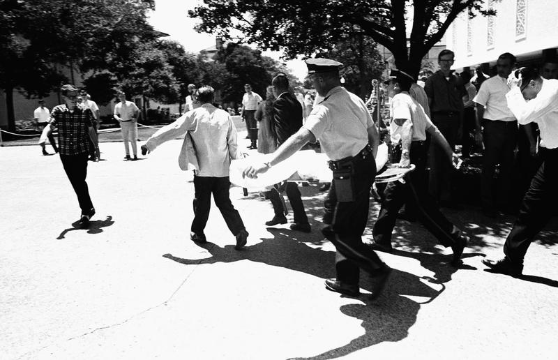 In this Aug. 1, 1966 file photo, one of the victims of Charles Joseph Whitman, the sniper who gunned down victims from a perch in the University of Texas tower, is carried across the campus to a waiting ambulance in Austin. (AP)