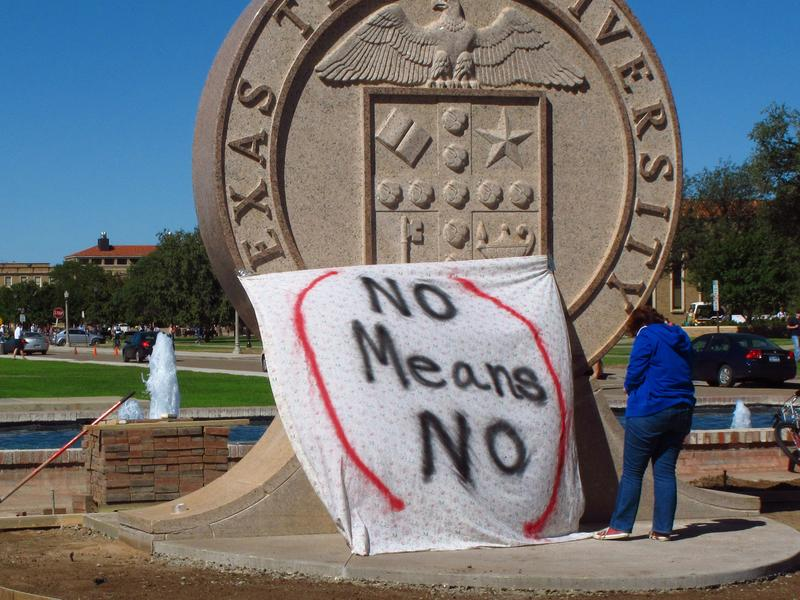 """Texas Tech freshman Regan Elder helps drape a bed sheet with the message """"No Means No"""" over the university's seal at the Lubbock, Texas campus in 2014 to protest what students say is a """"rape culture"""" on campus."""