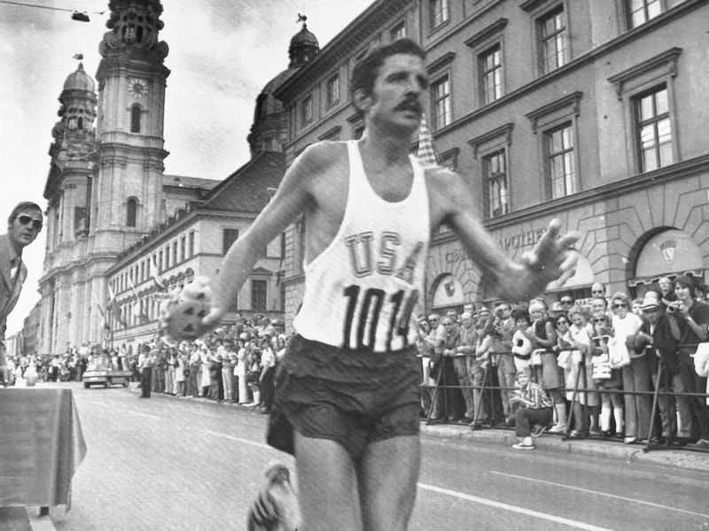 American Frank Shorter grabs a drink from a table while running through Munich in the 1972 Olympic marathon, which he won.