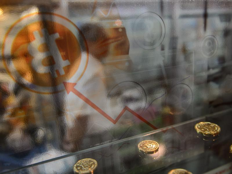 A man walks past a display cabinet containing models of bitcoins in Hong Kong on Wednesday.