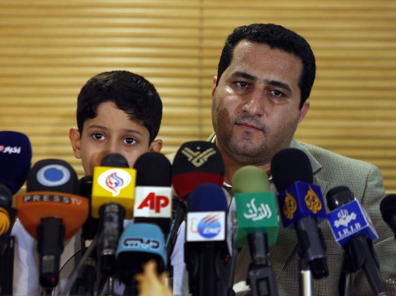 Shahram Amiri, an Iranian nuclear scientist, attends a news briefing while holding his son Amir Hossein as he arrives at the Imam Khomeini airport just outside Tehran, Iran, after returning from the United States in 2010.