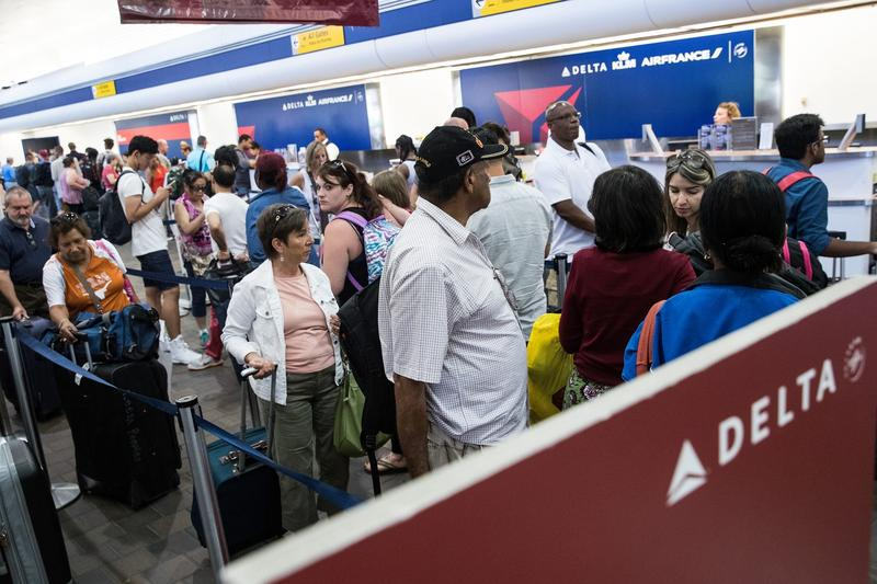 Travelers wait in line at the Delta check-in counter at LaGuardia Airport , Aug. 8, 2016 in the Queens borough of New York City. Delta flights around the globe were grounded and delayed on Monday morning due to a system outage. (Drew Angerer/Getty Images)