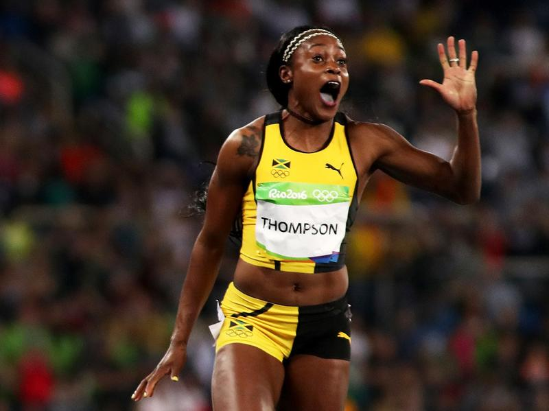Elaine Thompson of Jamaica (right) celebrates as she wins  the women's 100-meter final ahead of Tori Bowie of the United States, who took silver, and Shelly-Ann Fraser-Pryce of Jamaica, who got bronze.