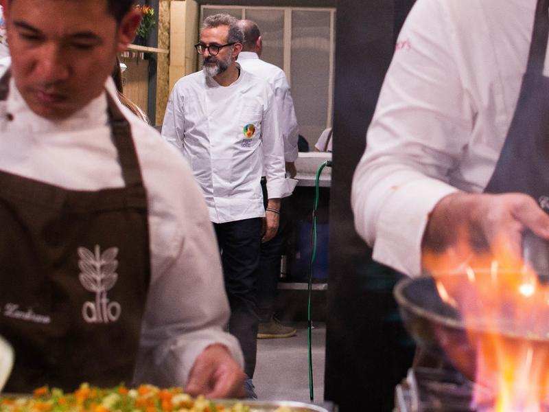 Chef Massimo Bottura checks with cooks as they prepare a gourmet soup kitchen dinner at RefettoRio Gastromotiva restaurant in Rio de Janeiro.