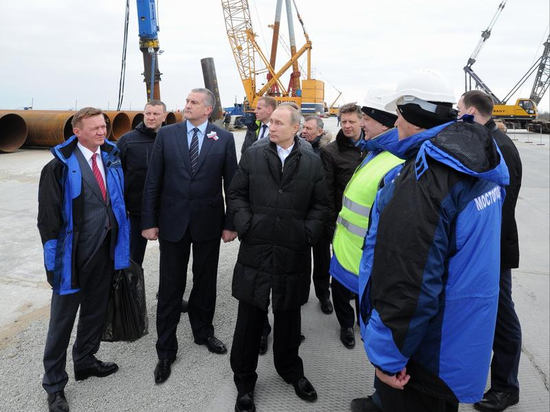 Russian President Vladimir Putin (center) joins Russia's federal highway agency head Roman Starovoit (left) and Crimean leader Sergei Aksyonov (second from left) on a visit to the Kerch Strait bridge construction site on Tuzla Island on March 18. The bridge will link Crimea to mainland Russia.