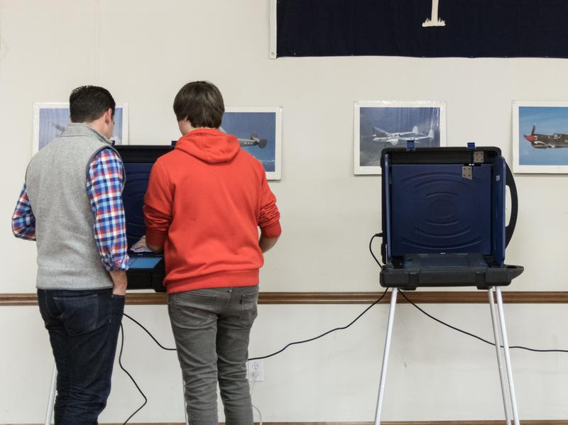 Polling station chairman helps a voter at a voting machine during the Republican presidential primary in February in West Columbia, S.C.