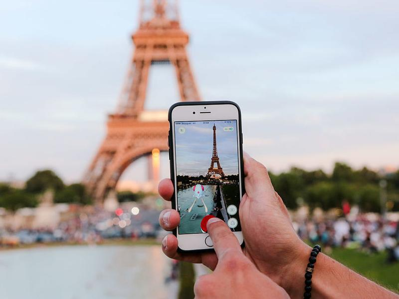 A man tries to catch a Pokémon while playing Nintendo's Pokémon Go augmented-reality game in front of the Eiffel Tower in Paris on Wednesday.