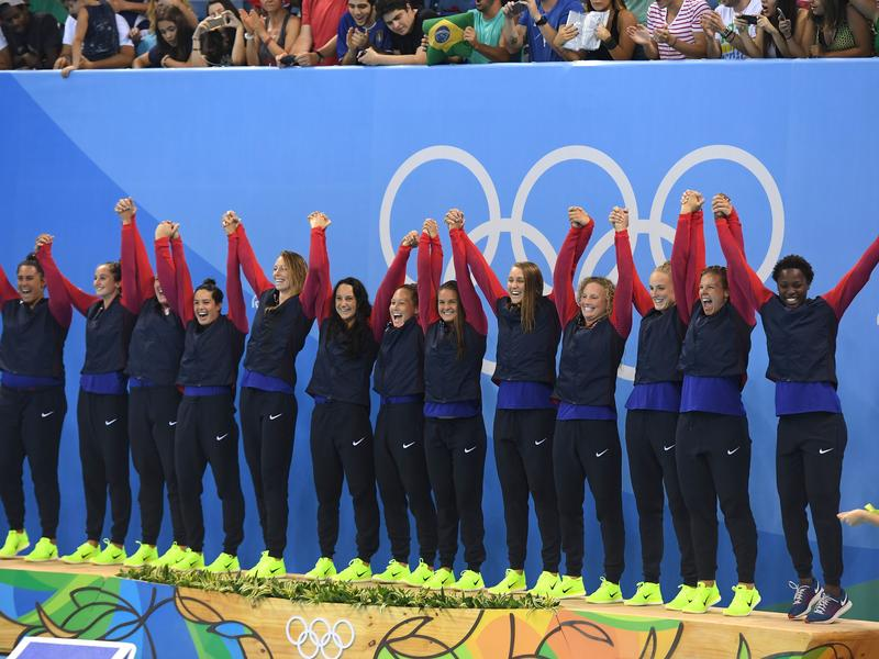 Gold medal winners on the U.S. women's water polo team celebrate on the podium after beating Italy in Rio de Janeiro Friday.