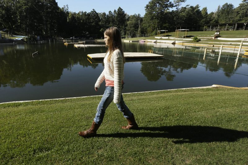 Kali Hardig, 12, survivor of a rare brain infection that is almost always fatal, walks past a lake at Willow Springs Water Park near Little Rock, Ark., Monday, Oct. 7, 2013. (Danny Johnston/AP)