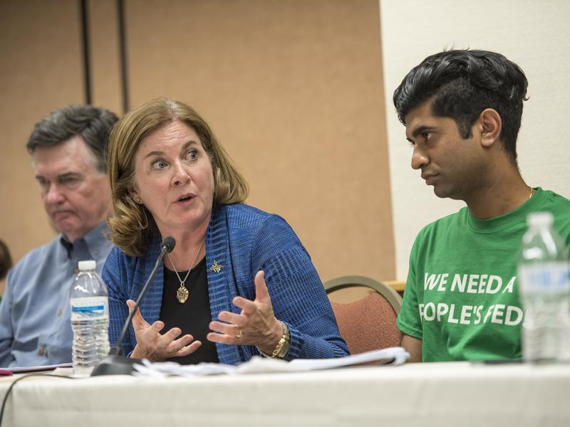 Esther George (center), president of the Kansas City Federal Reserve Bank, speaks as Shawn Sebastian (right), field director of the Fed Up coalition, listens Thursday during a meeting on the sidelines of an economic symposium in Jackson Hole, Wyo.