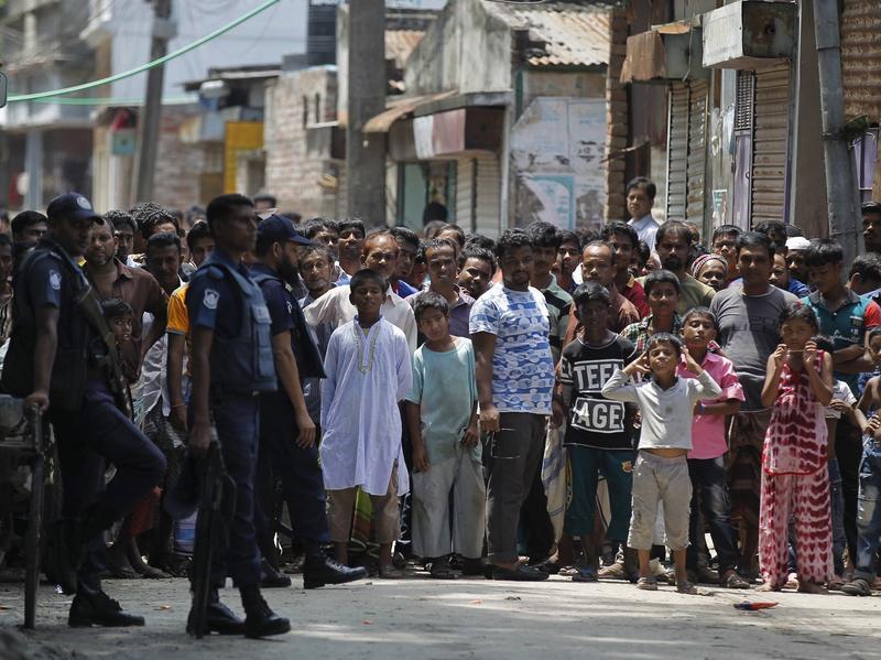Bangladeshis gather near the scene of the raid Saturday in Narayanganj, on the outskirts of Dhaka.