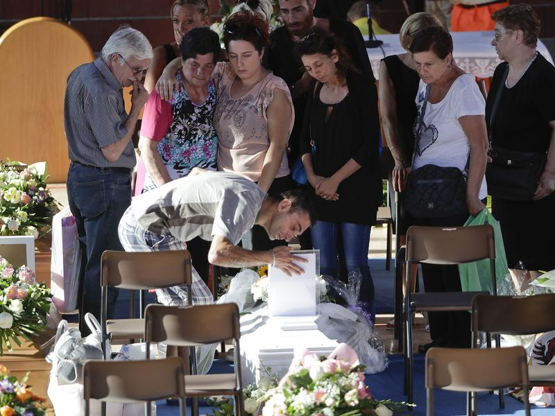 Relatives mourn over a coffin of one of the earthquake victims prior to the start of the funeral service on Saturday in Ascoli Piceno, Italy.