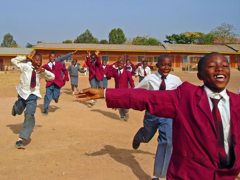 School children in Jos, Nigeria run across a field.