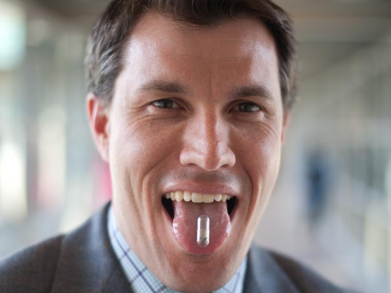 Chris Bettinger poses for a portrait with the edible battery his team designed at Carnegie Mellon University.
