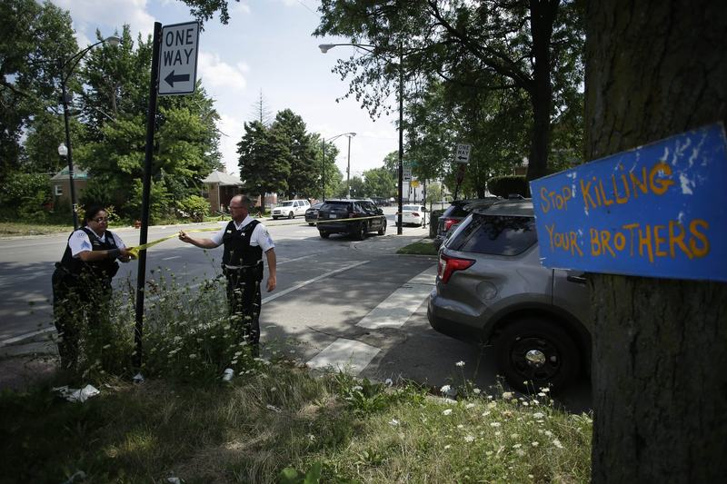 """A sign that reads """"Stop Killing Your Brothers"""" is displayed from a tree as Chicago Police officers hang yellow crime scene tape where a man was shot multiple times as he sat in a vehicle July 27, 2016 in Chicago. (Joshua Lott/Getty Images)"""