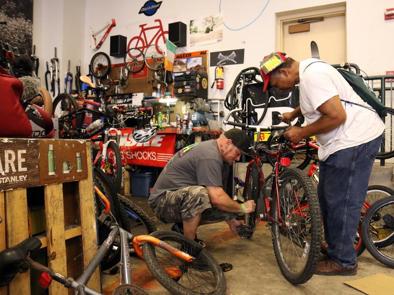 Jason Orth, manager of the Reading Bike Hub, fixes a bike for a customer.