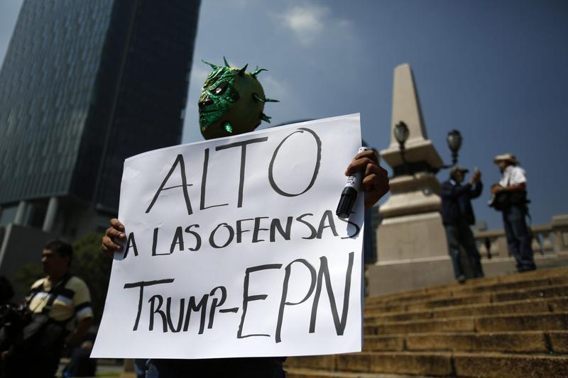 """Diego Garcia wears a Mexican wrestling mask and holds a sign reading in Spanish; """"Stop the offenses of Trump and EPN,"""" referring to Mexican President Enrique Pena Nieto, as he protests Donald Trump's meeting with the president, in Mexico City, Wednesday, Aug. 31, 2016. (Rebecca Blackwell/AP)"""