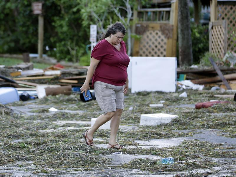 A resident checks on damage from Hurricane Hermine in Cedar Key, Fla. Hermine was downgraded to a tropical storm after it made landfall. Authorities say the storm could regain hurricane status by the time it hits the Mid-Atlantic states by Monday.