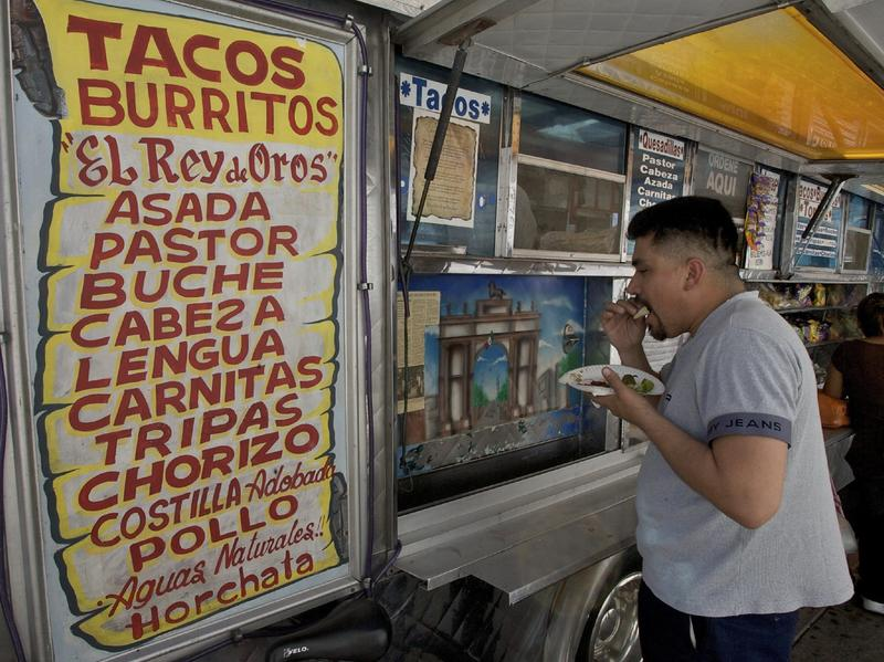 "Alejandro Flores eats a taco at ""El Rey de Oros"" taco truck in the Whittier district of east Los Angeles."
