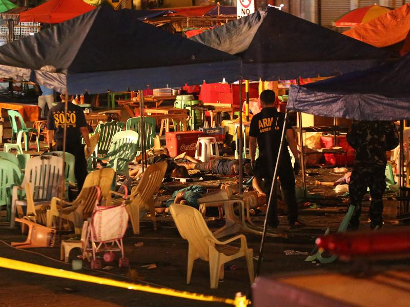 Philippine police officers investigate after an explosion at a night market that left about 10 people dead and wounded several others in southern Davao City, Philippines, late Friday.