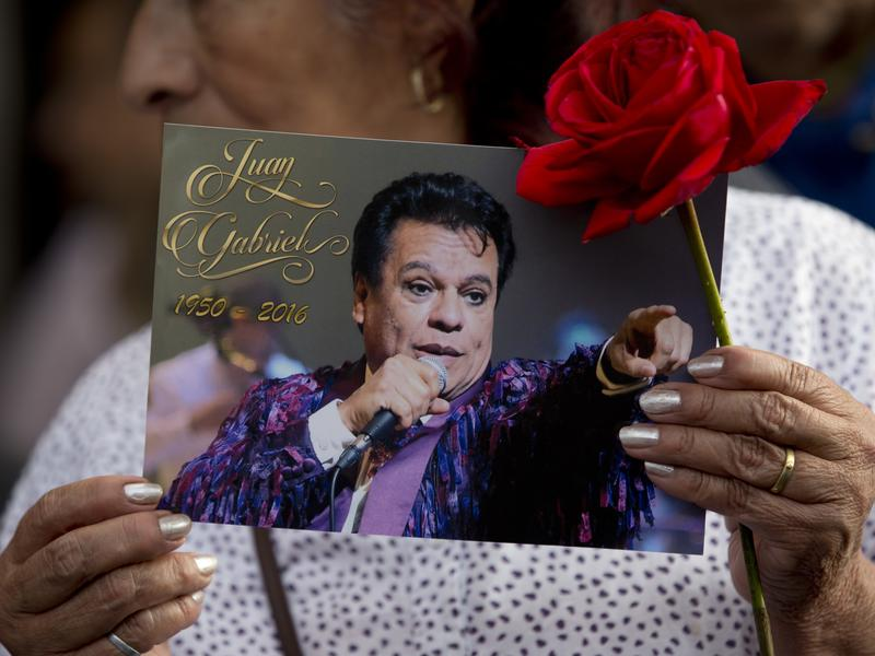 A woman holds a picture of Mexican songwriter and singer Juan Gabriel near a statue of him during a mass in Mexico City's Garibaldi plaza, Tuesday, Aug. 30, 2016.