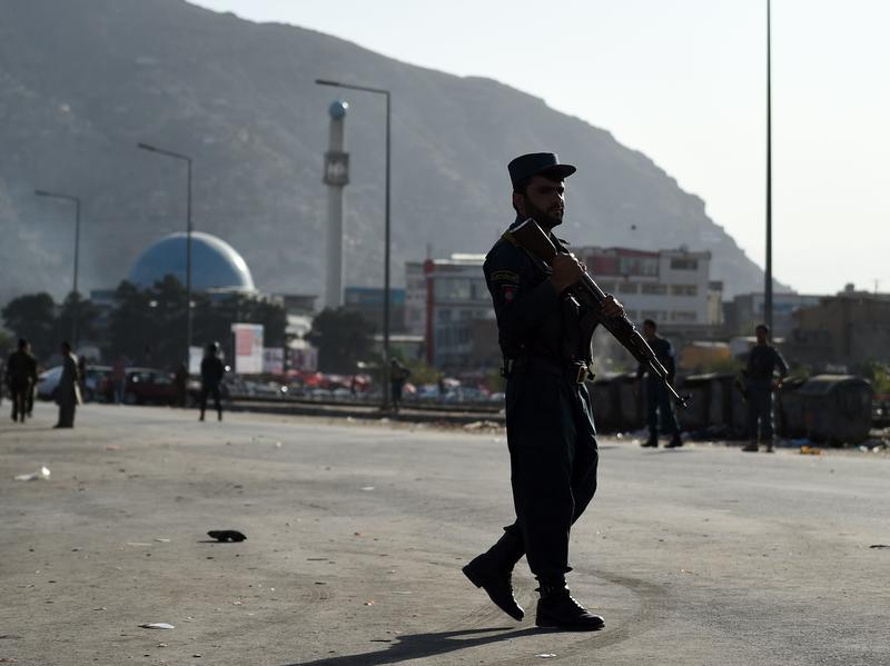 Afghan security personnel patrol at the site of twin suicide bombings near the Defense Ministry in Kabul, Afghanistan, on Monday.