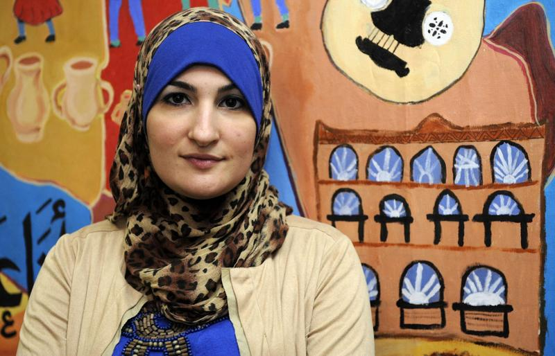 Linda Sarsour, director of the Arab American Association of New York, poses for photos in front of a canvas painted by the association's youth group at its headquarters in the Brooklyn borough of New York in December 2011. (Henny Ray Abrams/AP)