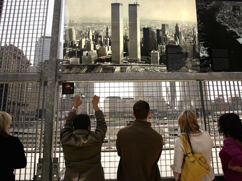 People look out at the former site of the World Trade Center in New York City in 2005, where construction had started on Freedom Tower.