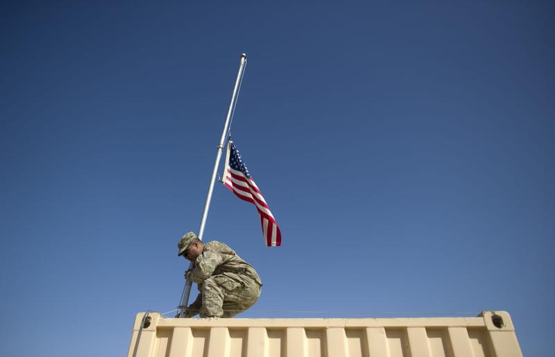 U.S. Army staff sergeant Chris Leota of Task Force 3-66 Bravo Company 172nd Infantry Brigade lowers the U.S. flag at Forward Operating Base Kushamond in Afghanistan on Sept. 11, 2011. (Johannes Eisele/AFP/Getty Images)