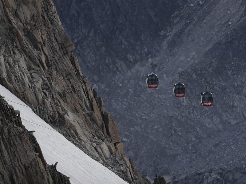 Stuck cable cars hang off the Mont Blanc massif between France and Italy on Friday. Dozens of tourists who were trapped in cable cars dangling above the Alps overnight, including a 10-year-old child, have all been safely rescued.