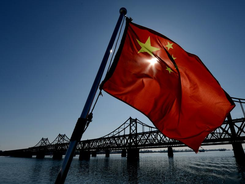 A Chinese flag flies on a boat next to the bridge that spans the Yalu River linking the North Korean town of Sinuiju with the Chinese town of Dandong. Most of North Korea's trade is with China, and much of it crosses the border here.